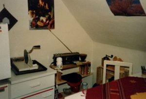 Küche der 80er Jahre: von links nach rechts: Ansatzweise kleiner Gefrierschrank, weißer Unterschrank mit handbetriebener Brotschneidemaschine. Ytonsteine und Holzbrett als Regal mit kleinem Radio darauf. Rechts in der Ecke eine Jaffa-Kiste mit alter Kaffeemühle. Im rechten Vordergrund: weißer Stuhl und ansatzweise erkennbarem Tisch auf dem eine rötliche Decke liegt.