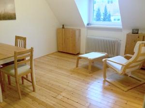 Minimalismus im Wohnzimmer: Links Tisch und 2 Stühle, rechts am Fenster: 2 Holzschränke und ein Sessel (Pöang von Ikea) mit Fußteil.