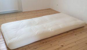 Auf einem Futon schlafen: Foto eines weissen Futons auf einem Holzdielenboden