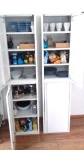 2 jeweils übereinander stehende weiße schmal Metallschränke. 3 von 4 Türen sind geöffnet. Zu sehen sind Geschirr, sowie einige Lebensmittel
