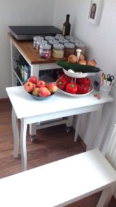Hinten ein Küchenwaagen mit Kochplatte. Daneben Gläser mit diversen Lebensmittelvorräten. Davor stehend ein Tisch mit Obst und Gemüse, sowie einem Köcher mit Stiften. Im Bildvordergrund eine Bank