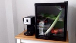 Minikühlschrank mit Glastür und einigen Lebensmitteln drin. Links davon stehend eine kleine Kaffemaschine.
