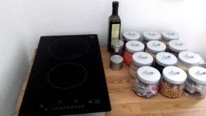 Links mobile Kochplatten (2er-Set, rechts Vorratsgläser und Flasche Öl. Alles auf einer Holzplatte stehend