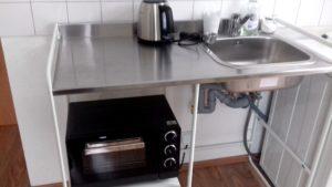 Spüle (mobil, Sunnersta von Ikea), darunter eine Ablagefläche mit einem Minibackofen. Auf der Spüle ein Wasserkocher.