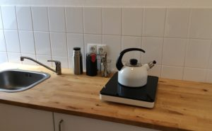 Blick auf die Holzarbeitsplatte mit links Spüle, dann Utensilien für Kaffee kochen, dann Einzelkochplatte mit Wasserkessel