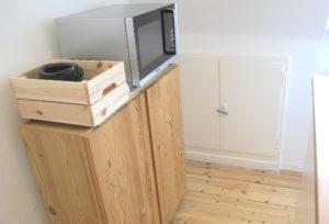 Holzschrank mit darauf stehender Mikrowelle