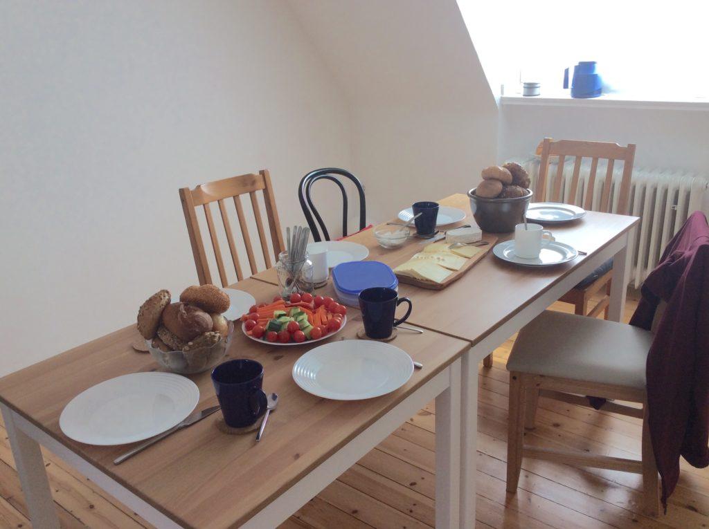 quadratischer und rechteckiger Esstisch als lange Esstafel in der Mitte des Raumes stehend.