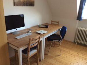 Ein quadratischer und ein rechteckiger Tisch nebeneinander stehend zu einem großen Schreibtisch.