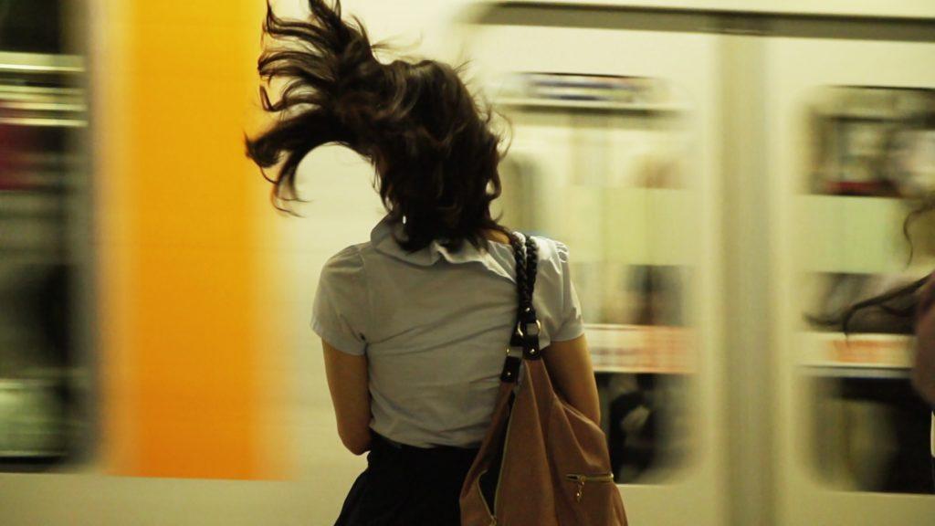 Frau von hinten fotografiert. Wehende Haare. Im Hintergrund verschwommen ein vorbeifahrender Zug.