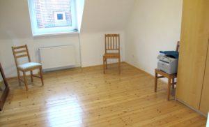 Blick in ein fast leeres Zimmer: 3 Stühle - auf einem Stuhl steht ein Drucker. Rechts im Bildrand ein Schrank. Am linken Bildrand ein unnutzer großer Spiegel.