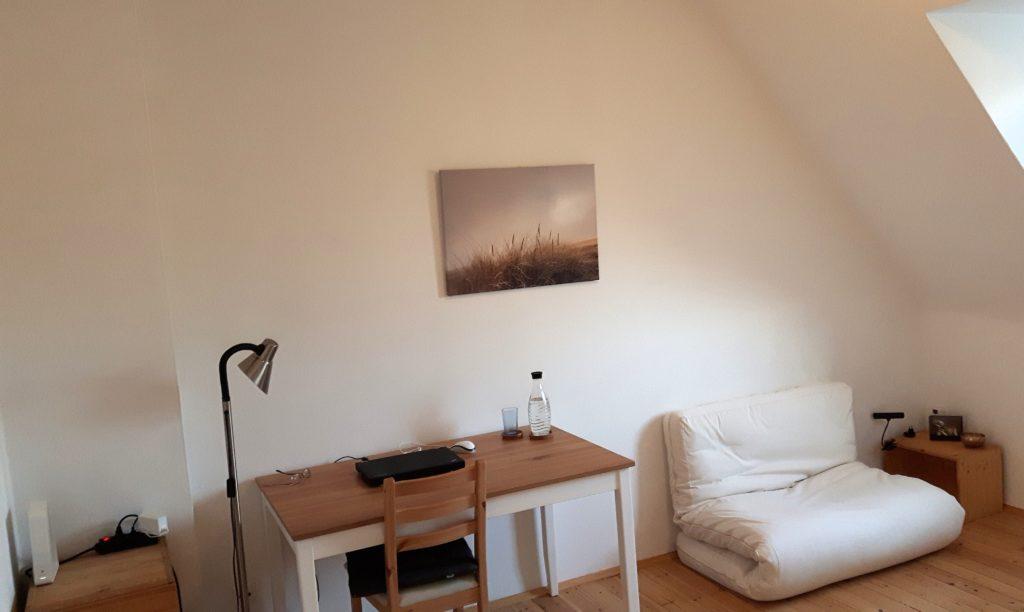 Blick ins Wohnzimmer: Kleine Kommode mit Wlan-Router und Steckerleiste. Daneben Stehlampe. Dann ein Tisch. Darauf ein Laptop, ein Glas, eine Glaskaraffe. Über dem Tisch an der Wand ein Bild mit Gräsern. Rechts vom Tisch ein zum Sofa zusammengefaltetes Futon. Rechts vom Futon: ein Hocker mit Bild, Klangschale, Lampe.