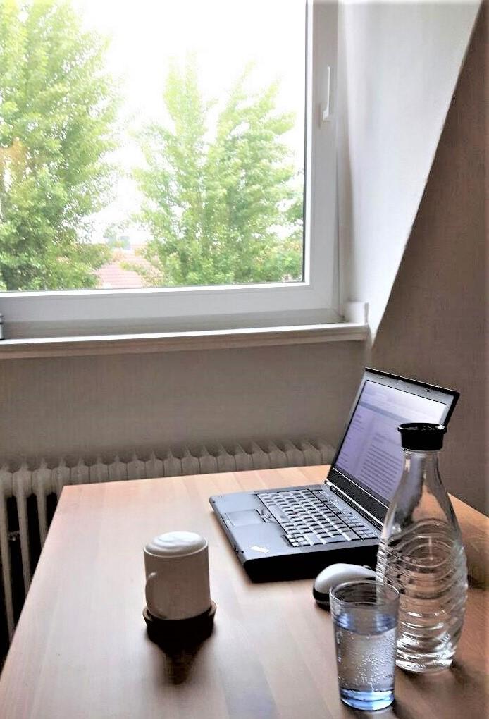 im Vordergrund ein Holztisch auf dem eine Kaffeetasse, Wasserflasche, Glas und Laptop stehen. Im Hintergrund ein Fenster. Es sind 2 Baumkronen zu erkennen.