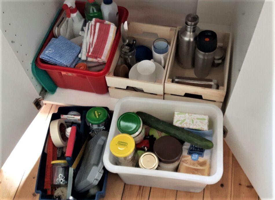 Blick in Küchenunterschrank: rote Kiste mit Putzuntensilien, 2 Holzkästen mit einigen Küchenutensilien. Vor dem Schrank stehend: 1 Werkzeugkiste, rechts daneben eine weiße Box mit Nahrungsmittelvorräten