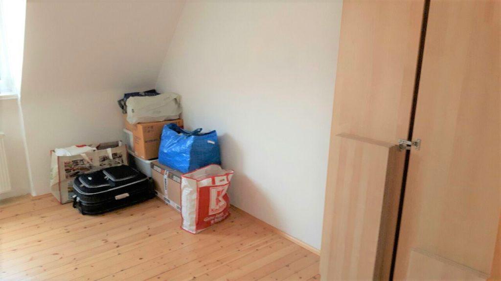 Eine Zimmerecke, in der 2 größere und 2 kleinere Kartons stehen, sowie 5 unterschiedlich große Taschen und 1 Koffer stehen. Am rechten Bildrand ein auseinander genommener Schrank.