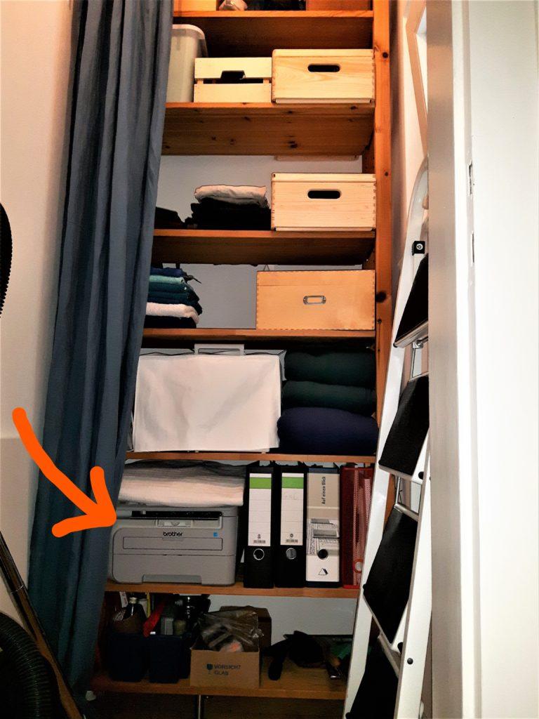 Blick auf das 2,26m hohe Holzregal in einer Abstellkammer. Im zweituntersten Regalfach links steht ein Drucker. Der Drucker ist mit einem Pfeil markiert.