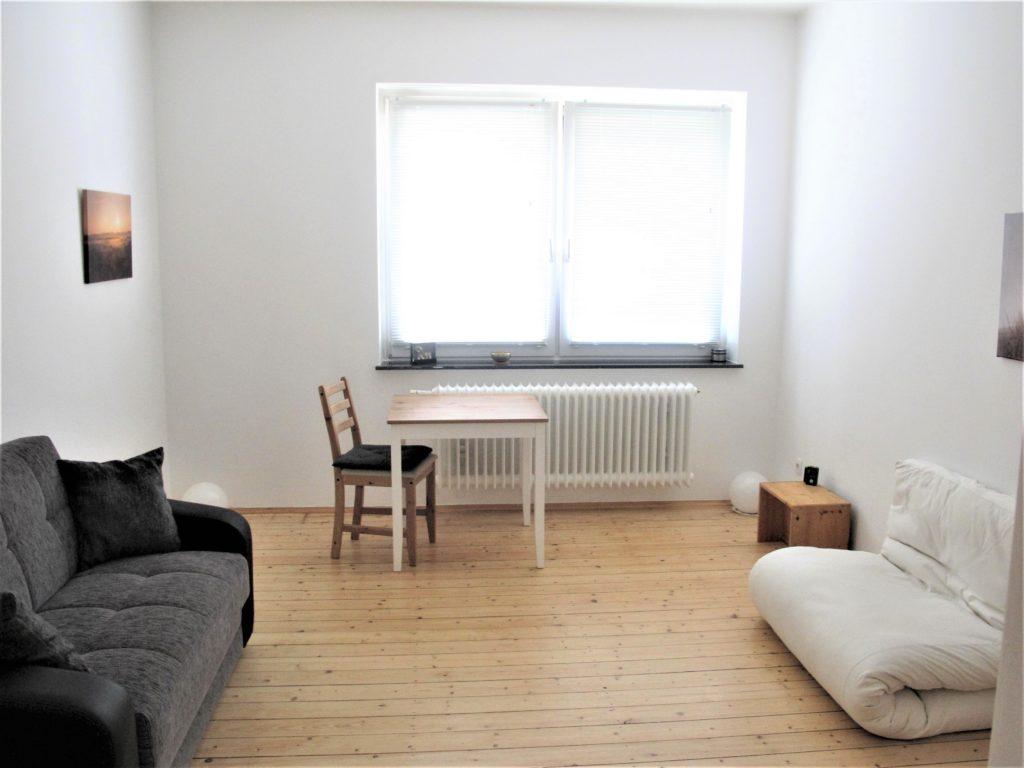 Wohnzimmer. Blick von der Tür aus Richtung Fenster. Links ein Sofa, am Fenster ein kleiner eckiger Tisch mit Stuhl. Rechts das Futon und der Berliner Hocker