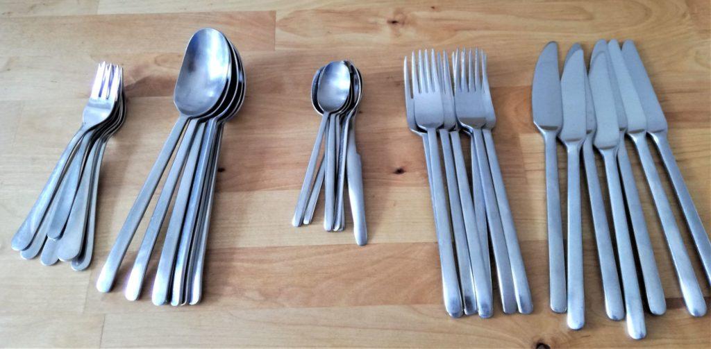 Besteck auf Holzplatte. Je 7 Messern, Gabeln, Esslöffel, Teelöffel, Kuchengabeln