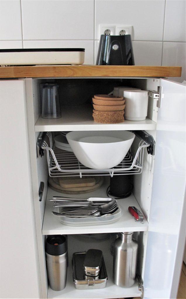 Küchenschrank mit 2 Einlegebrettern und einem Auszug. Oben: Gläser, Tassen, Korkuntersetzer, Auszug mit Porzellanschüssel und -schälchen, Teller, Mitte: Besteck in Plastikbehälter, Taschenmesser, 3 Brettchen, Kaffeemühle. Unten: Vorratsbehälter aus Edelstahl