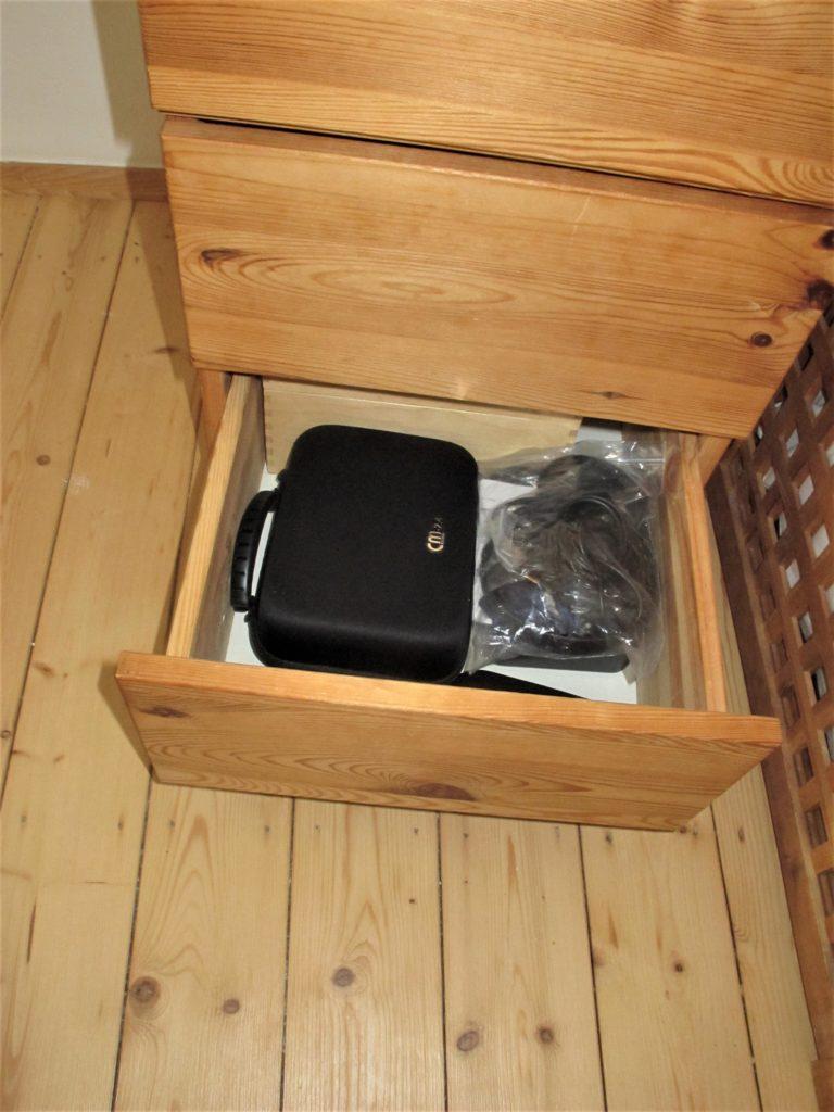 Schreibtischcontainer, untere Schublade mit Behälter für Hörgerätezubehör und eine durchsichtige Plastiktüte mit Kabeln. Im Hintergrund eine Holzkiste, darin ein Fotoapparat.