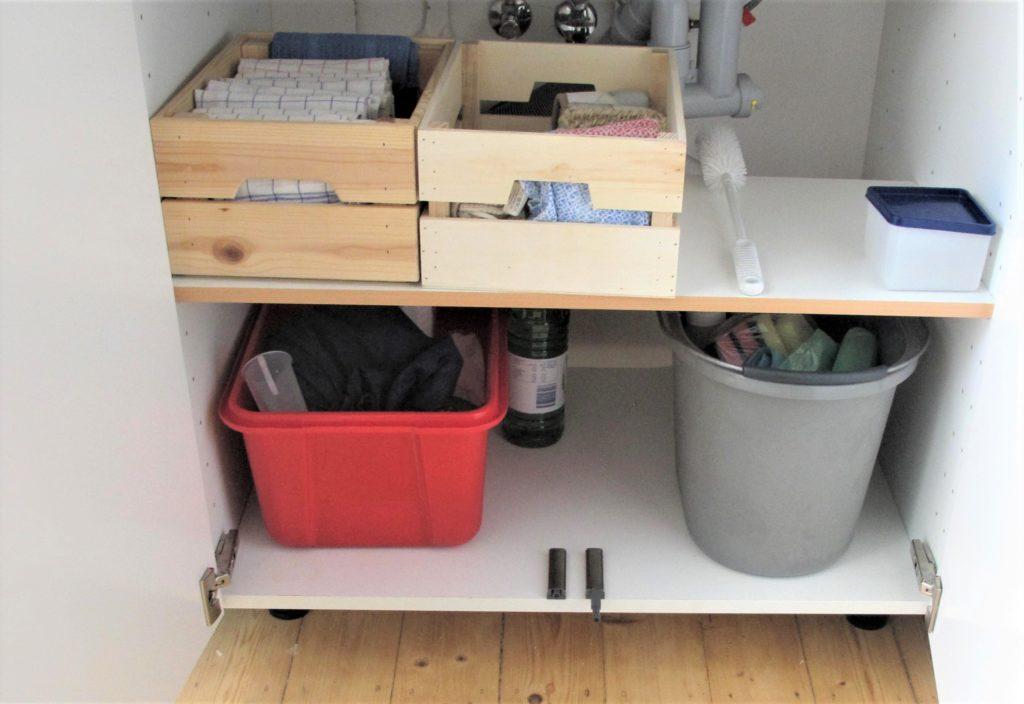 Spülenunterschrank mit 2 kleinen Kisten mit Trocken- und Putztüchern, Flaschenreiniger, eckigem Plastikbehälter, rote Box mit Waschmitteln, Eimer mit Putzmitteln