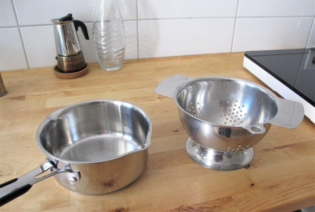Stieltopf und Durchschlag aus Edelstahl auf der Küchenarbeitsplatte stehend