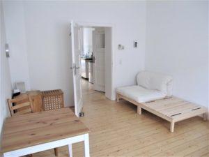Wohnschlafraum vom Fenster Richtung Tür fotografiert mit Podesten, Futon rechts und Tisch, Schreibtischcontainer und Holzbox links