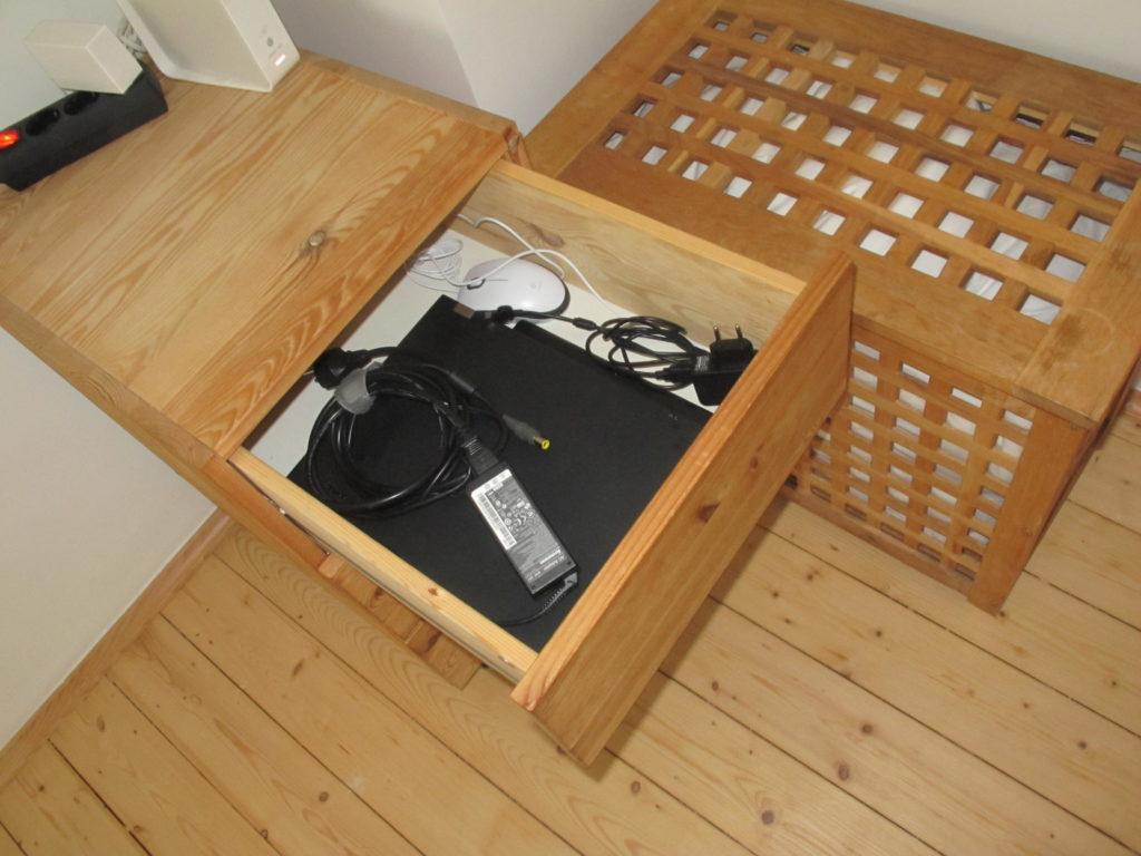 Schreibtischcontainer aus Holz. Von oben fotografiert mit geöffneter oberer Schublade. Darin ein Laptop