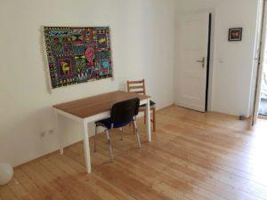 Weiße Wand mit buntem Wandteppich. Davor steht ein Tisch mit 2 Stühlen.