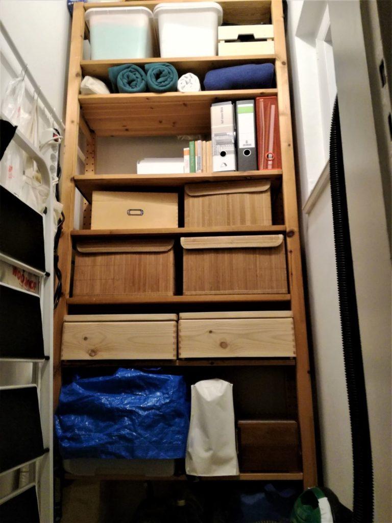 Blick auf ein Ivarregal mit verschiedenen Kisten, einigen Büchern und Aktenordnern.