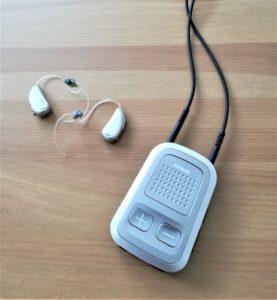 Hörgeräte und ein kleiner Audiostreamer auf einem Tisch liegend