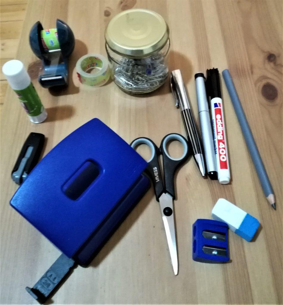 Kleinteile aus der schwarzen Kiste: Locher, USB-Stick, Klebestift, Klebefilmabroller, Glas mit Büroklammern, 1 Kugelschreiber, 1 Füller, 1 Bleistift, 1 Edding, 1 Radiergummmi, 1 Anspitzer
