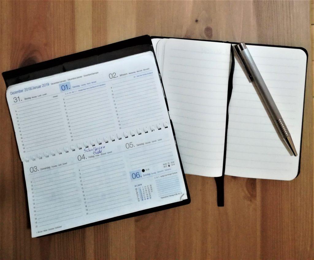Kalender, kleines Notizbuch und Kugelschreiber