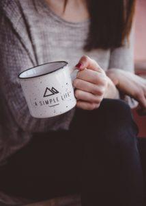 Foto einer nur teilweise sichtbaren Person, die eine Tasse festhält mit der Aufschrift: A simple Life