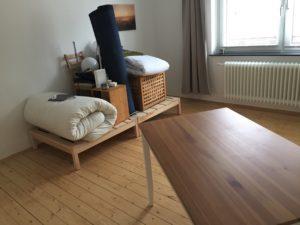 Blick auf 2 Holzpodeste auf denen Futon, Stühle, Teppich, Wäschebox, Hocker, Lampen und Bettzeug gestalpelt ist