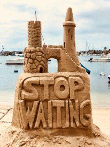 """Eine Sandburg mit der Aufschrift: """"Stop waiting"""""""