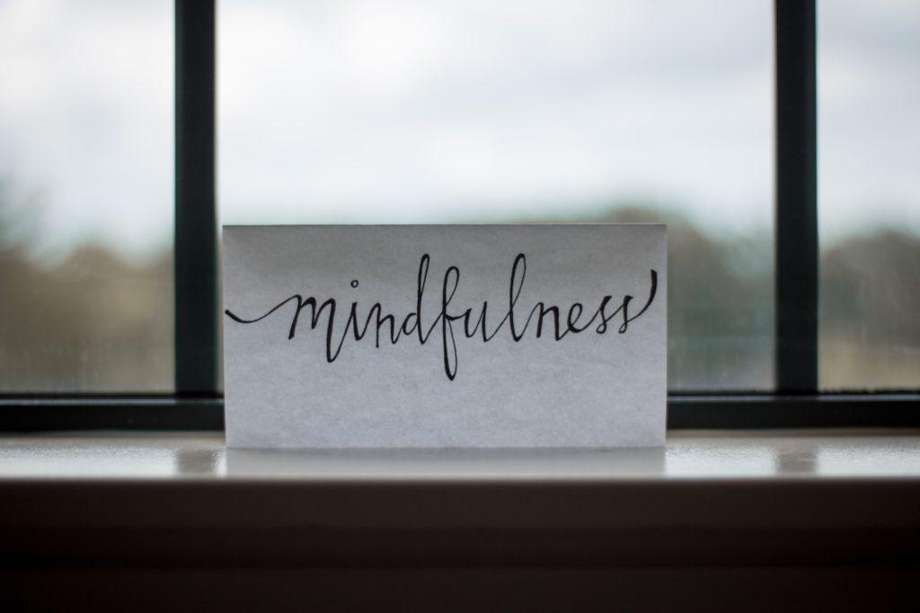 """handgeschriebenes Papier mit Aufschrift """"Mindfulness"""" an einem Fenster stehend."""