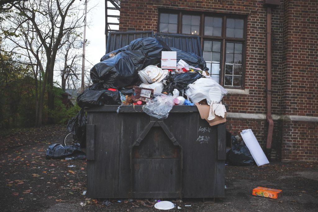 Offener Müllcontainer übersäät mit Müll vor einer Häuserwand