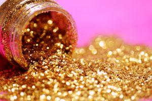 Goldener Glitzer mit umgekipptem Glas