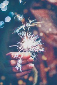 eine Hand hält eine brennende Wunderkerze