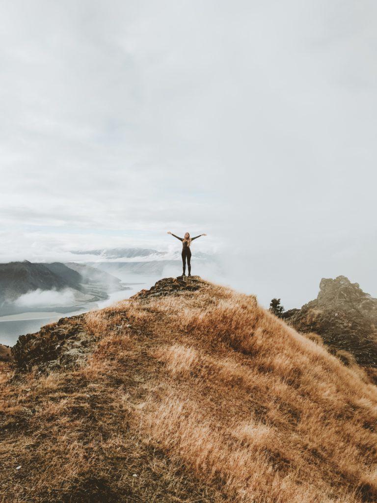 Person auf einem Grashügel stehend und beide Hände in die Luft streckend