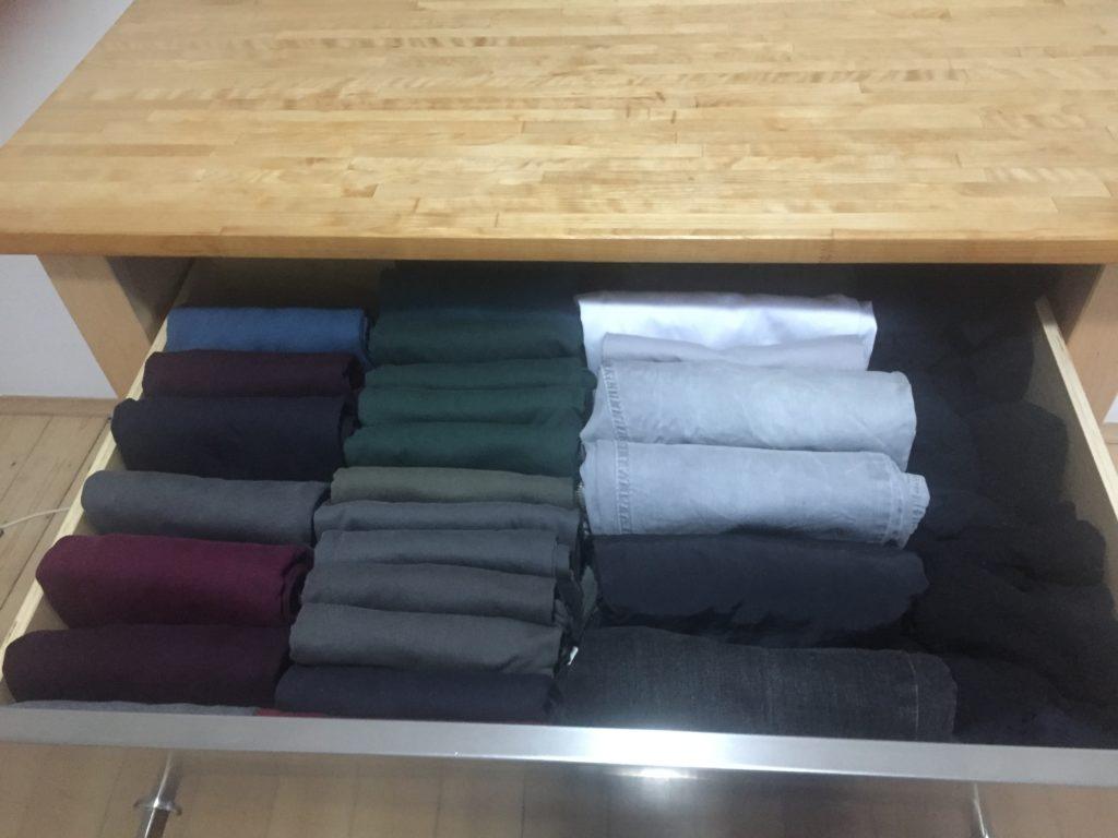 geöffnete Schublade eines Schubladenschrankes mit gefalteten T-Shirts und Hosen