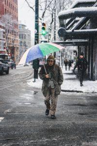 Mann mit Regenschirm überquert bei Schneeregen eine Straße