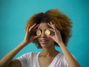 eine Frau hält zwei goldfarbene Bitcoin-Münzen vor ihre Augen