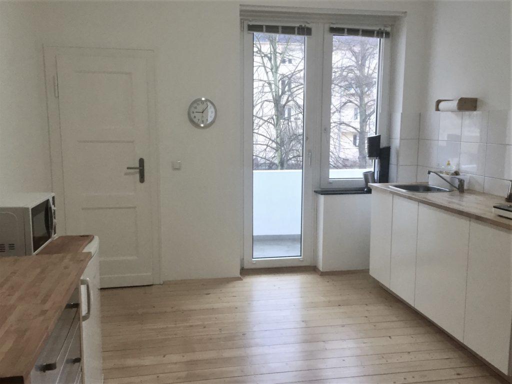 Blick in die Küche, Richtung Fensterfront: Links Schubladenschrank und Kühlschrank, rechts 3 weiße Unterschränke mit Holzarbeitsplatte und Spüle, sowie Kochplatte.