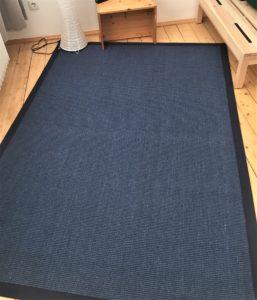 blauer Sisalteppich auf Holzdielenboden
