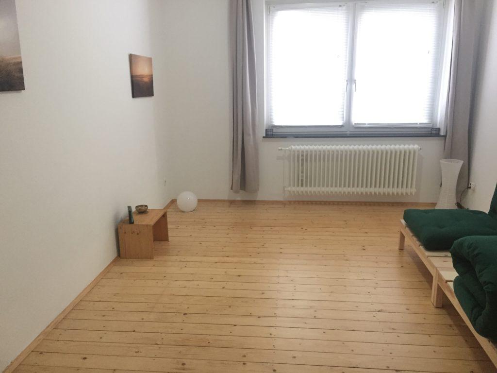 Zimmer mit Holzdielenboden, einem Hocker 2 Bildern. Am rechten Bildrand ist ansatzweise ein grünes Futon zu sehen