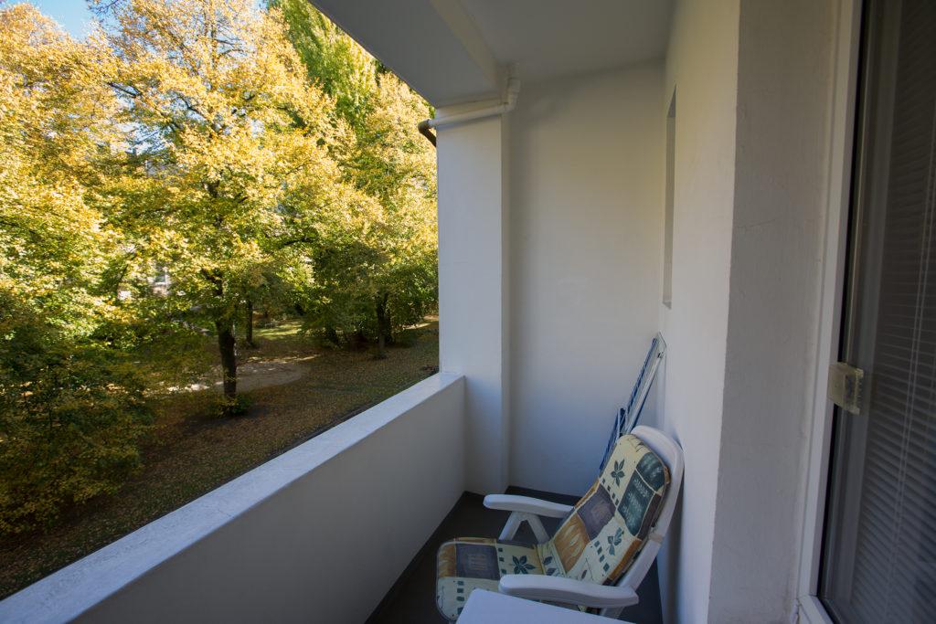 Üerdachter Balkon mit Balkonstuhl und Blick in einen Innenhof mit großen Bäumen