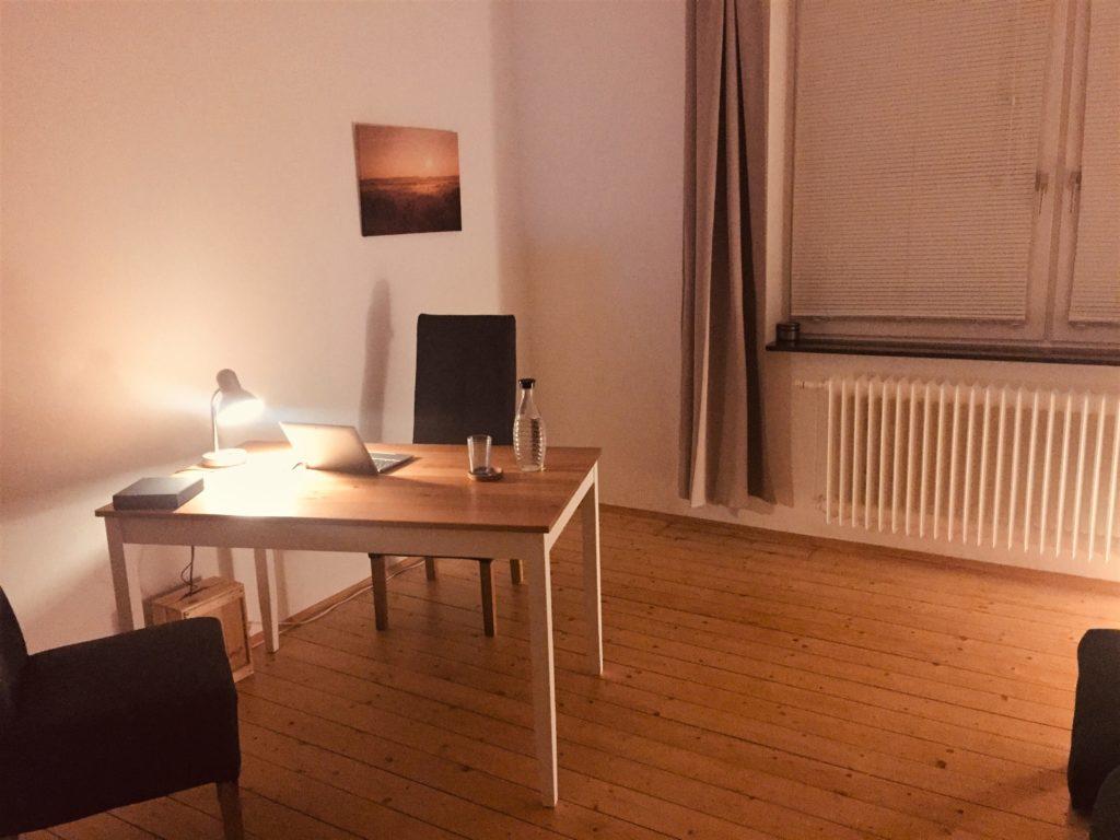 Foto mit abendlicher Stimmung: Tisch mit 2 Stühlen und Laptop und kleiner Lampe. Im Hintergrund ein Fenster.