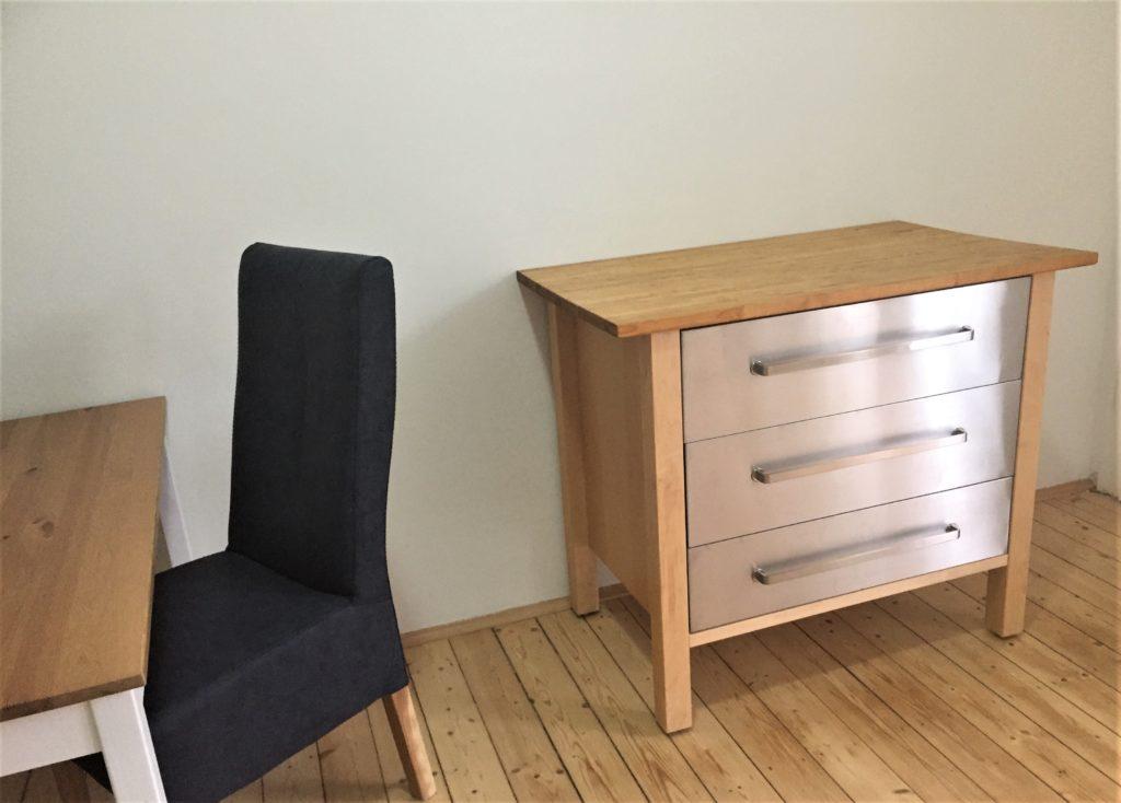 Eine ca. 1m breite Kommode mit 3 silbernen Schubladen. Am linken Bildrand ein Stuhl und ansatzweise ein Tisch.
