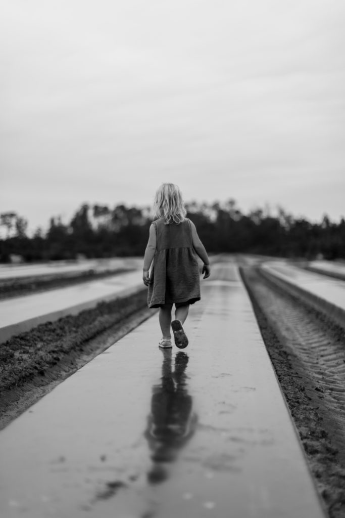 Kleines Mädchen auf einem Weg gehend